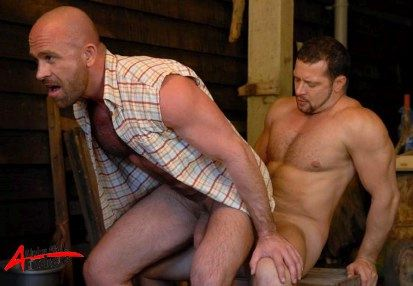 Hunky bald stud with a hard dick sitting on his buddy's cock
