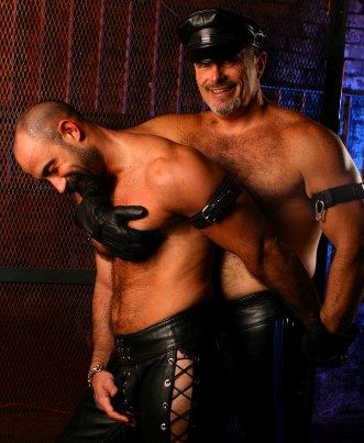 Two leather men smile as they embraced