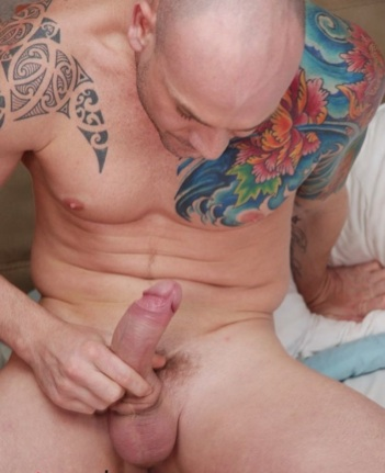 Inked muscle boy Kurt Rogers plays with his hard uncut dick