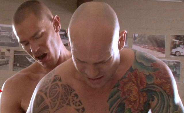 Tattooed bald guy bends over, getting fucked