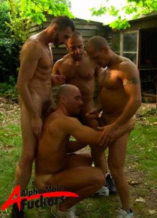 Big beefy guy squatting down in front of three naked studs