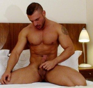 Masculine muscle hunk jacking on a a bed