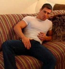 Hot studly Rick Bauer on a couch fully clothed