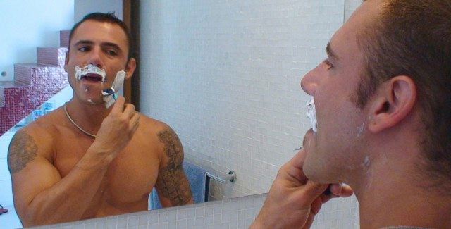 Pedro Adreas looks at himself in a mirror as he shaves