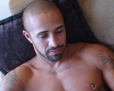 Scruffy inked Latin boy in bed