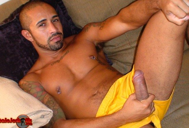 Inked Latin guy beats his thick meat as it pokes out of his shorts
