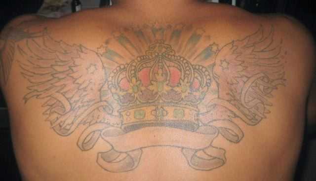 Ink work on the back of muscled Latin guy