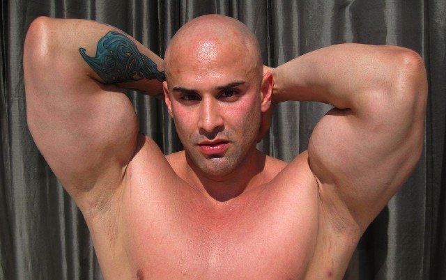 Bald bodybuilder shows huge biceps