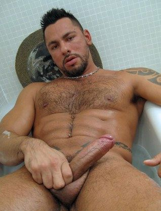 Beefy Latin guy strokes his hard uncut cock in bathtub