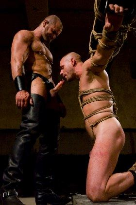 bound slave on knees sucking booted master's cock