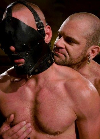 hooded slave with master behind him
