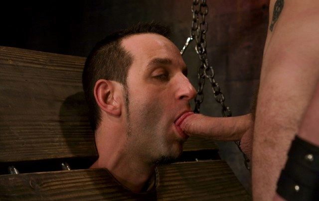 Locked in the stocks, Jason Miller is forced to suck Wolfs cock