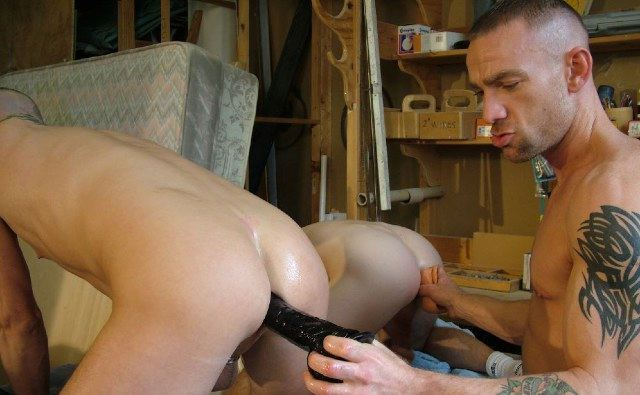 Tattood stud Darren Robins plugs up a couple of smooth asses with two big dildoes