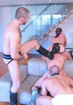 Booted scruffy guy in jock forces another guy to eat ass