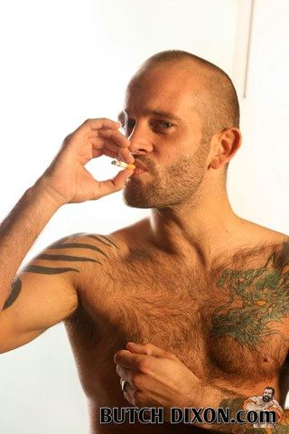 Masculine hairy tattooed guy smoking a cigarette