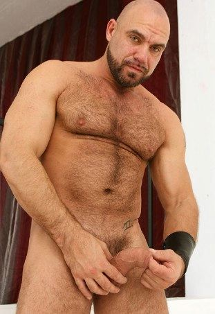 Hairy hunk Axel Ryder grabs his thick cock and stares into the camera