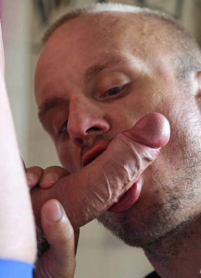 Cocksucker working a rock hard uncut cock with the foreskin pulled back