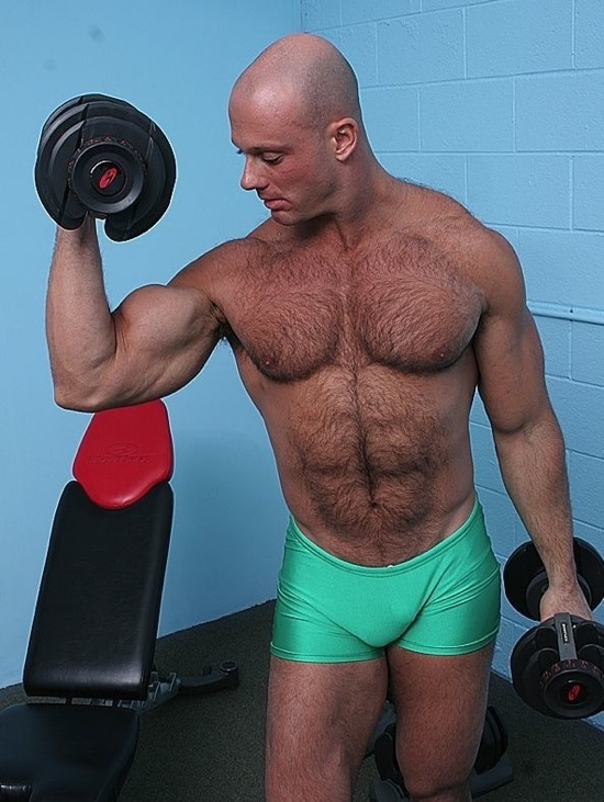 Bald hunk working out shirtless