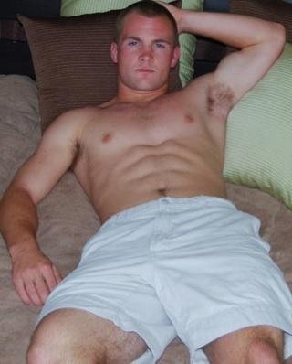 Ian, un chico musculoso, yace sin camisa