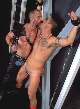 Scott Samson kissed while tied down to a St. Andrews Cross