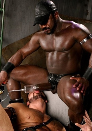 Lee Mane pumps his fat cock while Mick Powers licks the pump