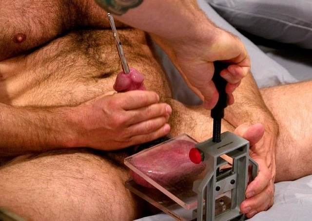 Luke's balls pressed into a vice, with a sounding rod in his dick