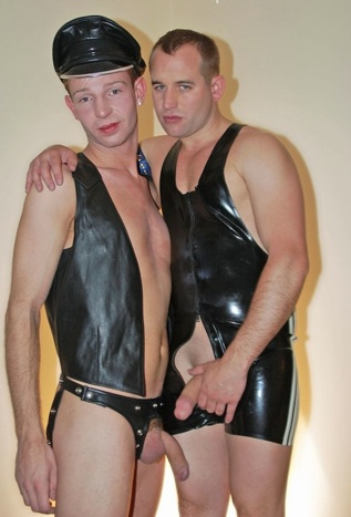 Justyn and Jasper in fetish gear play with their big cocks