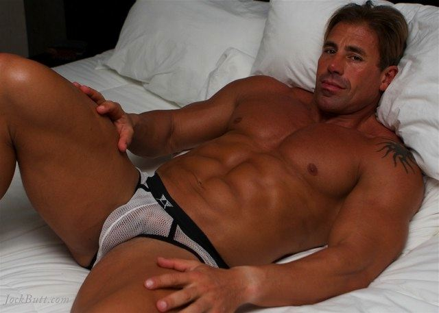 Beefy body builder laying in bed in his mesh briefs