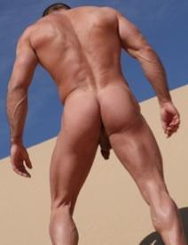 Hombre musculoso escalando una duna de arena