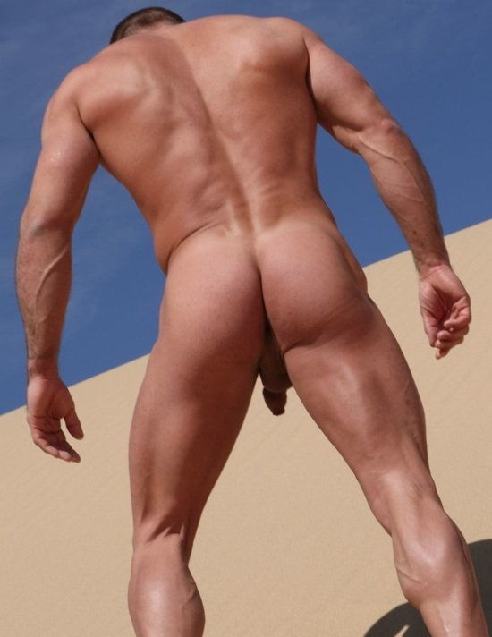 Muscle man climbing up a sand dune