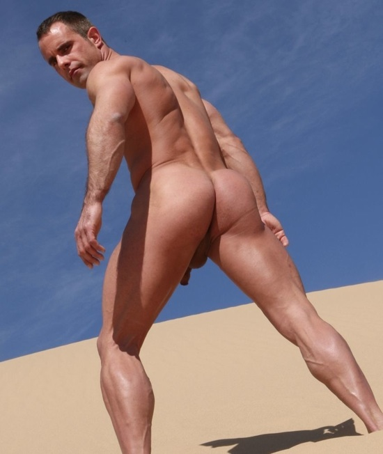 Hot masculine musclar guy on a sand dune