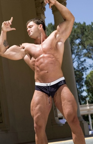 Culturista tatuado muestra sus musculosos brazos