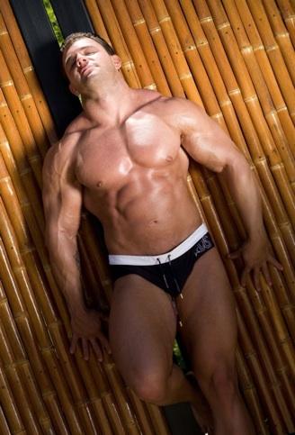 Culturista musculoso presume sus brazos y piernas