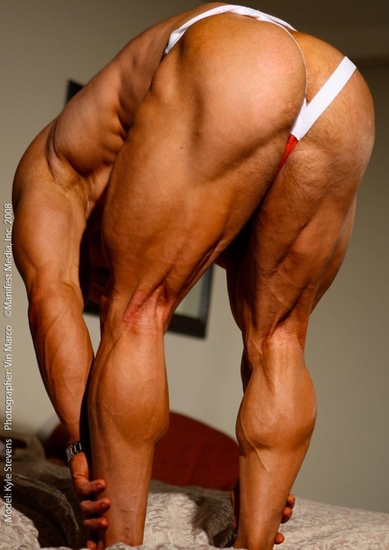 Bodybuilder Kyle Stevens bends over to show his muscular legs and ass