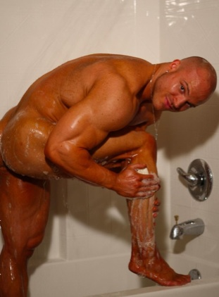 Bodybuilder Kyle Stevens in the shower with soap on his muscular legs