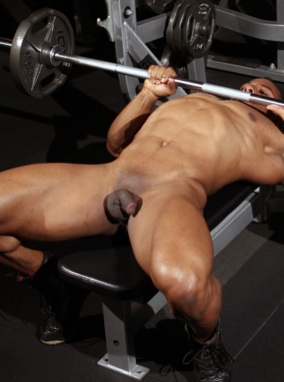 Smooth ripped  bodybuilder Alan Demond bench pressing named in the gym