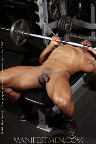 Un moreno muy musculoso levanta pesas