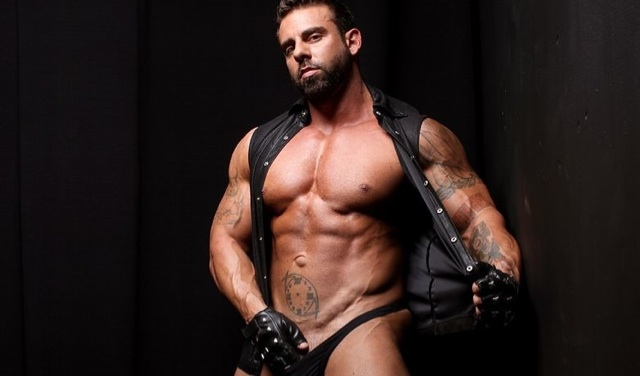 Xavier shows off his massive chest and inked arms