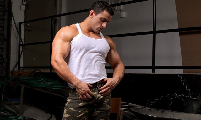 Latin bodybuilder flexing his shoulders and biceps