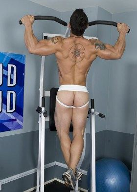 Inked muscle boy working out in jock