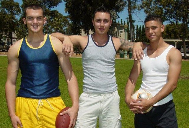 Three young college guys on a sports field