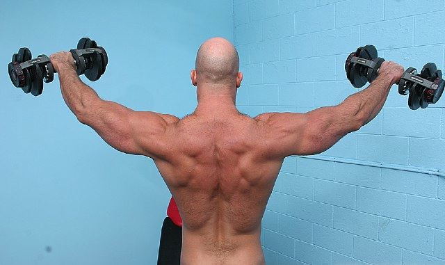 Bald muscle boy lifting weights