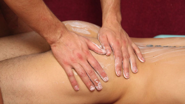 Guy gives other guy a massage with hand cream