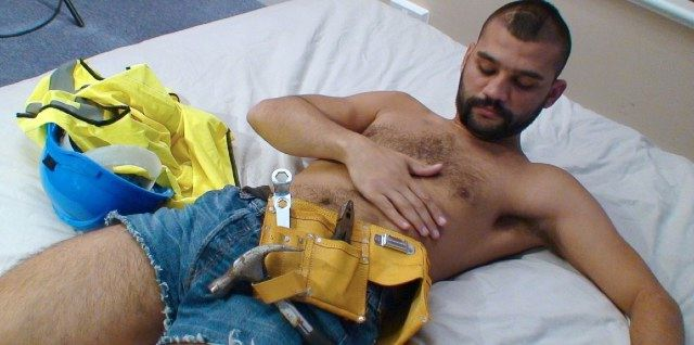 Hairy young construction worker cresses his chest