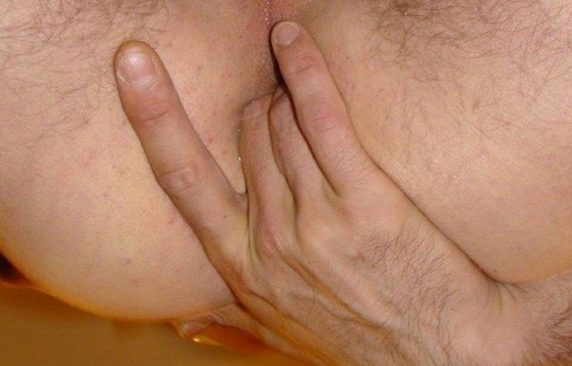 Bottom lubing his shaved hole up with two fingers.