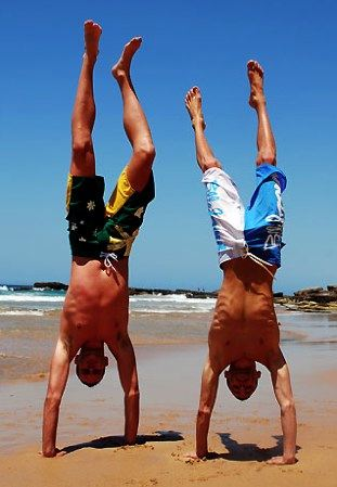 Two guys on the beach doing hand stands
