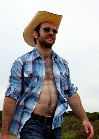 Shirtless scruffy young cowboy