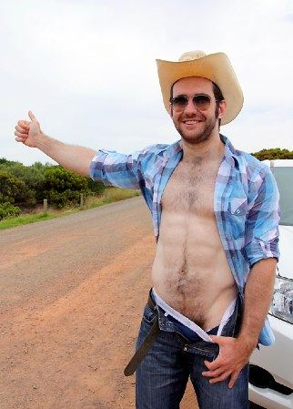 Scruffy muscle boy hitchiking on the side of the road