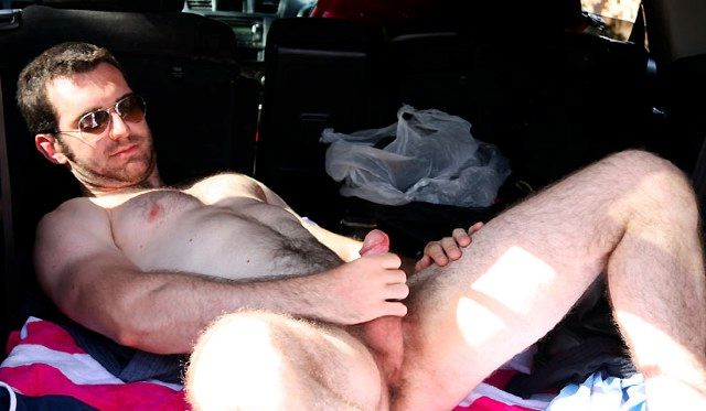 Scruffy young guy strokes his dick in the back of a car