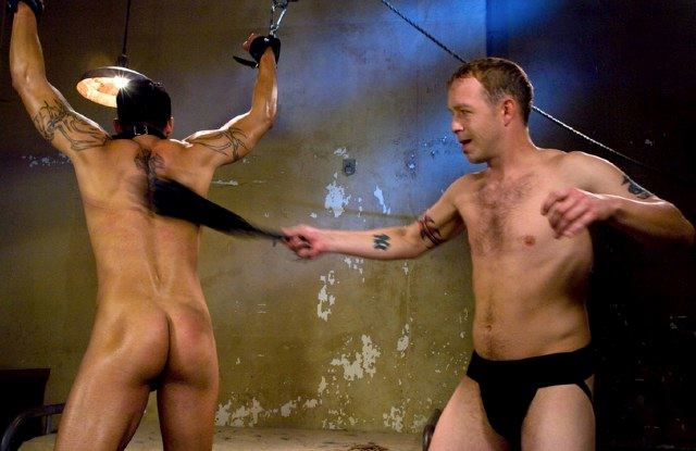 A naked, collared, and bound young Ash Brooks is flogged by Rod Barry in a jockstrap